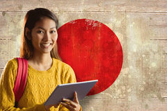 Composite image of smiling asian female student using tablet Royalty Free Stock Photos