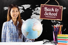 Composite image of smiling asian woman holding a globe Royalty Free Stock Photo