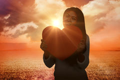 Composite image of smiling asian woman holding paper heart Royalty Free Stock Images