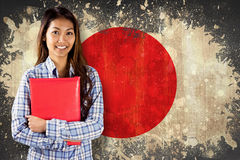 Composite image of smiling asian woman holding red book Royalty Free Stock Photos