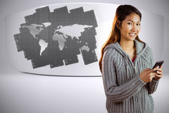 Composite image of smiling asian woman using smartphone Stock Image