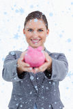 Composite image of smiling bank clerk offering piggy bank Royalty Free Stock Photo
