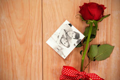 Composite image of smiling beatiful couple sitting on a sofa. Smiling beatiful couple sitting on a sofa against red heart envelope and a red rose Stock Photos