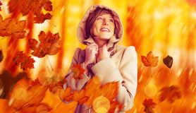 Composite image of smiling beautiful woman in winter coat looking up Royalty Free Stock Images