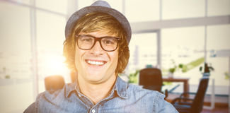 Composite image of smiling blond hipster staring at camera. Smiling blond hipster staring at camera against board room Stock Image