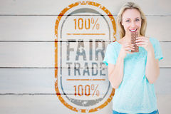 Composite image of smiling blonde eating bar of chocolate. Smiling blonde eating bar of chocolate against painted blue wooden planks royalty free stock photography