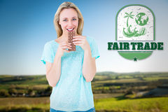 Composite image of smiling blonde eating bar of chocolate. Smiling blonde eating bar of chocolate against scenic landscape royalty free stock photos