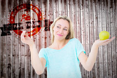 Composite image of smiling blonde holding bar of chocolate and apple. Smiling blonde holding bar of chocolate and apple against wooden planks royalty free stock photos