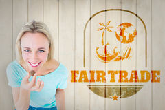 Composite image of smiling blonde holding box of chocolates. Smiling blonde holding box of chocolates against wooden planks royalty free stock images