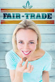 Composite image of smiling blonde holding box of chocolates. Smiling blonde holding box of chocolates against wooden planks royalty free stock photos