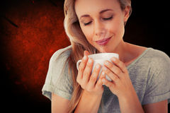 Composite image of smiling blonde with hot beverage relaxing Royalty Free Stock Photo