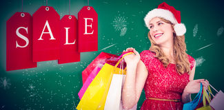 Composite image of smiling blonde in santa hat holding shopping bags Royalty Free Stock Image