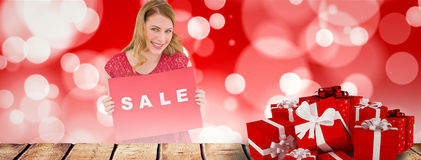 Composite image of smiling blonde showing a red sale poster Royalty Free Stock Photo