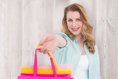 Composite image of smiling blonde woman offering shopping bags Stock Images