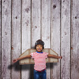 Composite image of smiling boy pretending to be pilot. Smiling boy pretending to be pilot against digitally generated grey wooden planks Stock Image