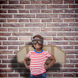 Composite image of smiling boy pretending to be pilot. Smiling boy pretending to be pilot against red brick wall Royalty Free Stock Photos