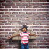 Composite image of smiling boy pretending to be pilot. Smiling boy pretending to be pilot against red brick wall Royalty Free Stock Image