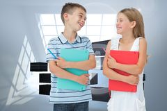 Composite image of smiling brother and sister holding their exercise books Stock Photo
