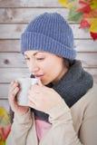 Composite image of smiling brunette drinking hot beverage Stock Image