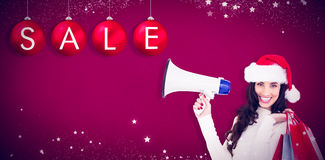 Composite image of smiling brunette holding gift bags and megaphone Royalty Free Stock Photo