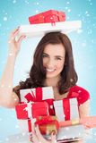 Composite image of smiling brunette holding many gifts Stock Images