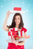 Composite image of smiling brunette holding many gifts Stock Image