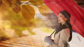 Composite image of smiling brunette holding red umbrella Royalty Free Stock Photography
