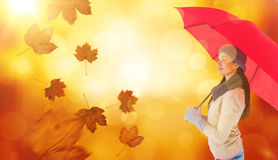 Composite image of smiling brunette holding red umbrella Stock Photos