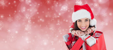 Composite image of smiling brunette holding shopping bags full of gifts Stock Photo