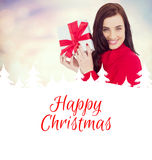 Composite image of smiling brunette in red jumper hat showing a gift Royalty Free Stock Images