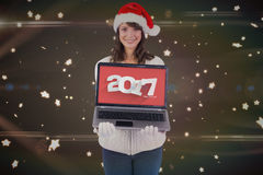 Composite image of smiling brunette in santa hat showing her laptop Royalty Free Stock Photo