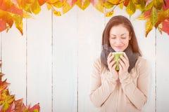 Composite image of smiling brunette smelling hot beverage Stock Photography