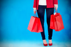 Composite image of smiling brunette in winter clothes holding shopping bags Royalty Free Stock Photo