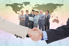 Composite image of smiling business people shaking hands while looking at the camera Royalty Free Stock Images