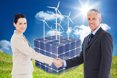 Composite image of smiling business people shaking hands while looking at the camera Stock Photos