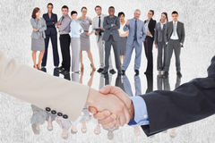 Composite image of smiling business people shaking hands while looking at the camera Royalty Free Stock Photography