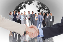 Composite image of smiling business people shaking hands while looking at the camera Stock Photo