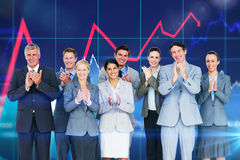 Composite image of smiling business team applauding at camera Stock Images