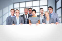 Composite image of smiling business team holding poster Royalty Free Stock Photo