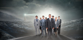 Composite image of smiling business team looking at camera Royalty Free Stock Photo
