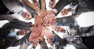 Composite image of smiling business team standing in circle hands together Royalty Free Stock Photos