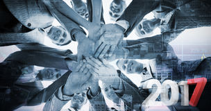 Composite image of smiling business team standing in circle hands together Royalty Free Stock Images