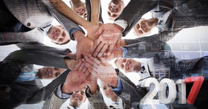 Composite image of smiling business team standing in circle hands together Royalty Free Stock Image