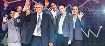 Composite image of smiling business team waving at camera Royalty Free Stock Images