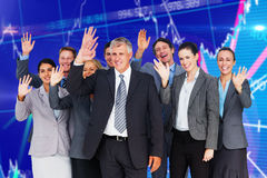 Composite image of smiling business team waving at camera Stock Photos
