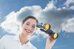 Composite image of smiling business woman with binoculars Royalty Free Stock Photography