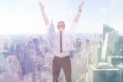 Composite image of smiling businessman cheering with his hands up. Smiling businessman cheering with his hands up against city skyline Stock Photos