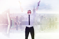 Composite image of smiling businessman cheering with his hands up. Smiling businessman cheering with his hands up against room with large window looking on city Stock Photo