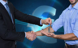 Composite image of smiling businessman giving keys and shaking hands Royalty Free Stock Image