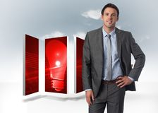 Composite image of smiling businessman with hand on hip Royalty Free Stock Image